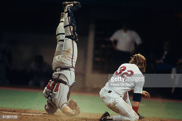 Dan Gladden of the Minnesota Twins knocks over catcher Greg Olson of the Atlanta Braves at home base as the run is settled at home base during the...