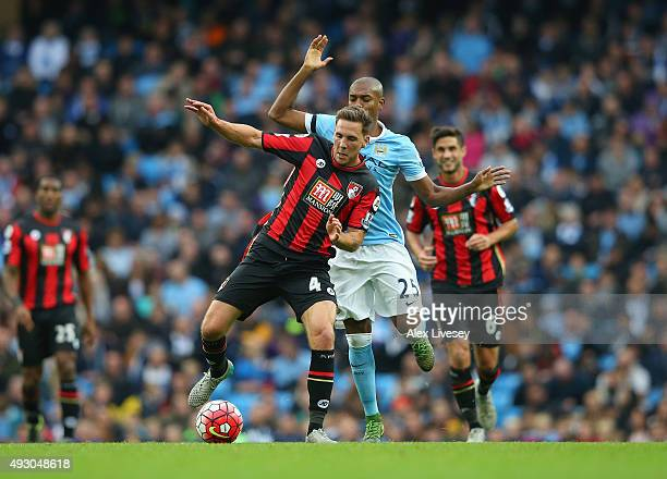 Dan Gosling of Bournemouth and Fernandinho of Manchester City compete for the ball during the Barclays Premier League match between Manchester City...