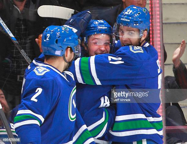 Dan Hamhuis and Brandon Sutter congratulate Jake Virtanen of the Vancouver Canucks who scored his first NHL goal against the Philadelphia Flyers...