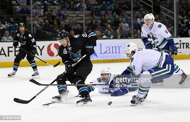 Dan Hamhuis and Chris Tanev of the Vancouver Canucks steal the puck from Joonas Donskoi of the San Jose Sharks at SAP Center on March 31 2016 in San...