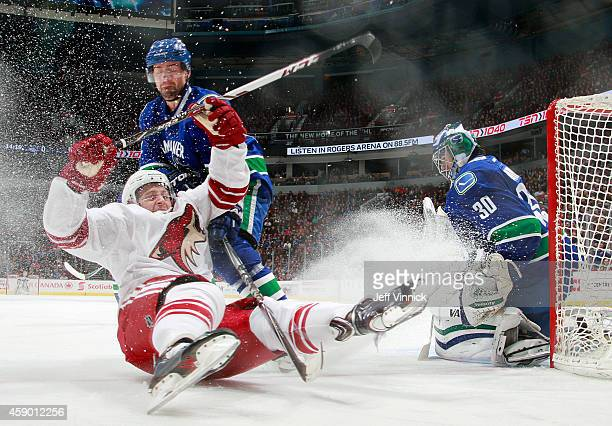 Dan Hamhuis and Ryan Miller of the Vancouver Canucks watch Brandon McMillan of the Arizona Coyotes slide into the boards during their NHL game at...