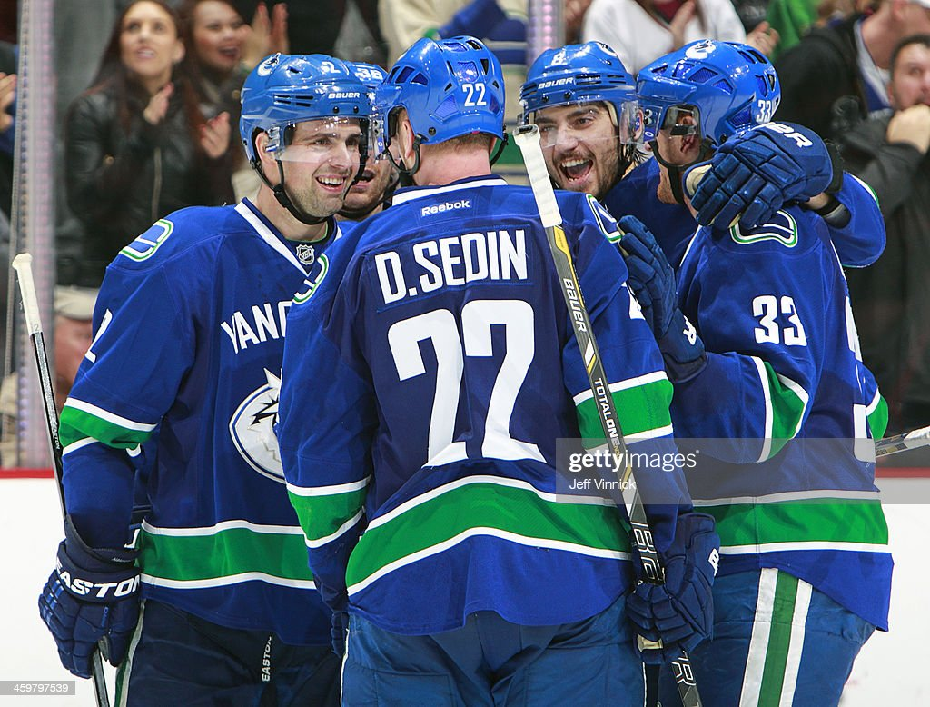 Dan Hamhuis #2, Christopher Tanev #8 and Henrik Sedin #33 of the Vancouver Canucks celebrate with Daniel Sedin #22 after his goal against the Philadelphia Flyers during an NHL game at Rogers Arena December 30, 2013 in Vancouver, British Columbia, Canada. Philadelphia won 4-3.