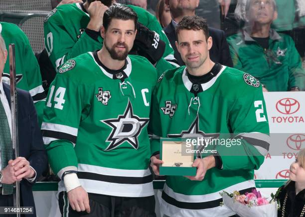 Dan Hamhuis of the Dallas Stars is honored and presented with a gift from teammate Jamie Benn for playing in his 1000th career game during a pregame...