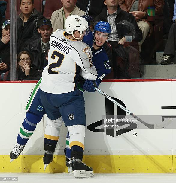 Dan Hamhuis of the Nashville Predators checks Alex Burrows of the Vancouver Canucks during their game at General Motors Place on January 11 2010 in...