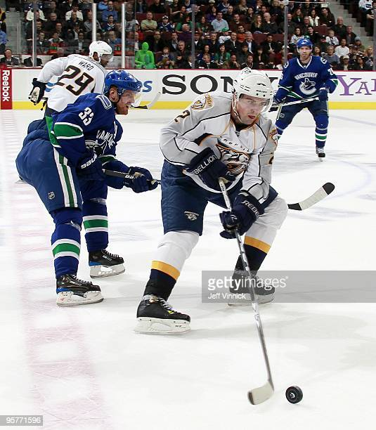 Dan Hamhuis of the Nashville Predators is checked by Henrik Sedin of the Vancouver Canucks during their game at General Motors Place on January 11...