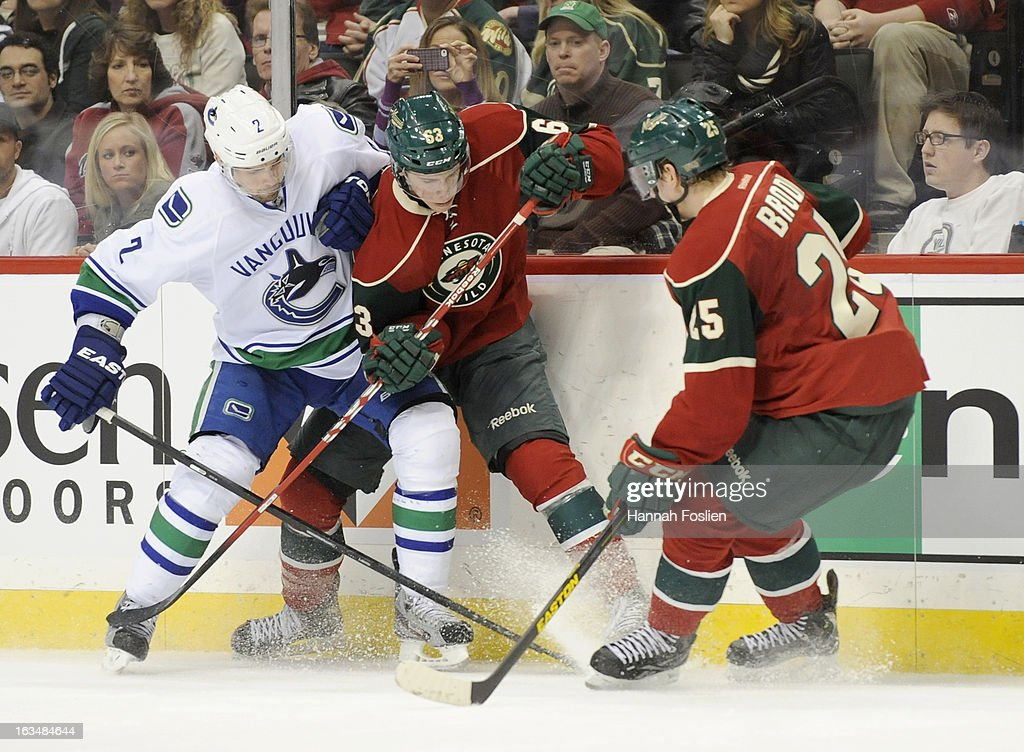 Dan Hamhuis #2 of the Vancouver Canucks and Charlie Coyle #63 of the Minnesota Wild fight for control of the puck against the boards as Jonas Brodin #25 of the Minnesota Wild looks on during the second period of the game on March 10, 2013 at Xcel Energy Center in St Paul, Minnesota.