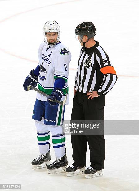 Dan Hamhuis of the Vancouver Canucks and referee Kevin Pollock chat during a second period stoppage in play against the Winnipeg Jets at the MTS...