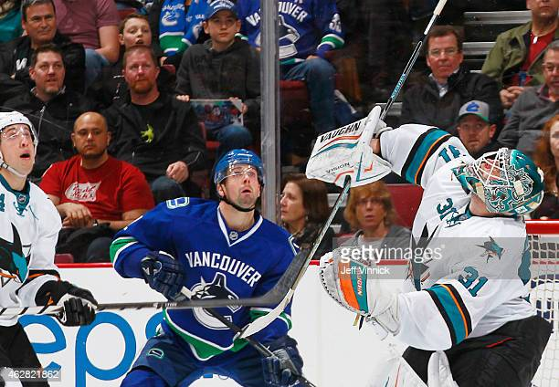 Dan Hamhuis of the Vancouver Canucks Brenden Dillon and Antti Niemi of the San Jose Sharks look up for the puck during their NHL game at Rogers Arena...