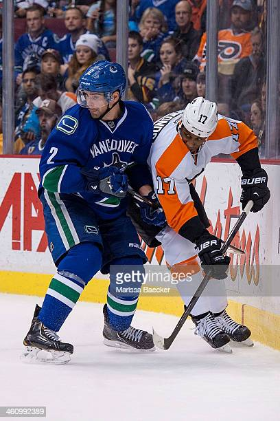 Dan Hamhuis of the Vancouver Canucks checks Wayne Simmonds of the Philadelphia Flyers into the boards on December 30 2013 at Rogers Arena in...