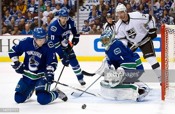 Dan Hamhuis of the Vancouver Canucks clears the loose puck after blocking a shot as goalie Roberto Luongo and Ryan Kesler of the Vancouver Canucks...