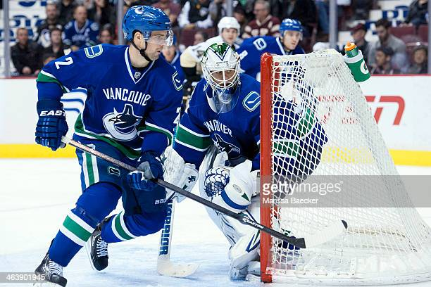 Dan Hamhuis of the Vancouver Canucks skates around the net of Eddie Lack as he defends against the Pittsburgh Penguins on January 7, 2014 at Rogers...