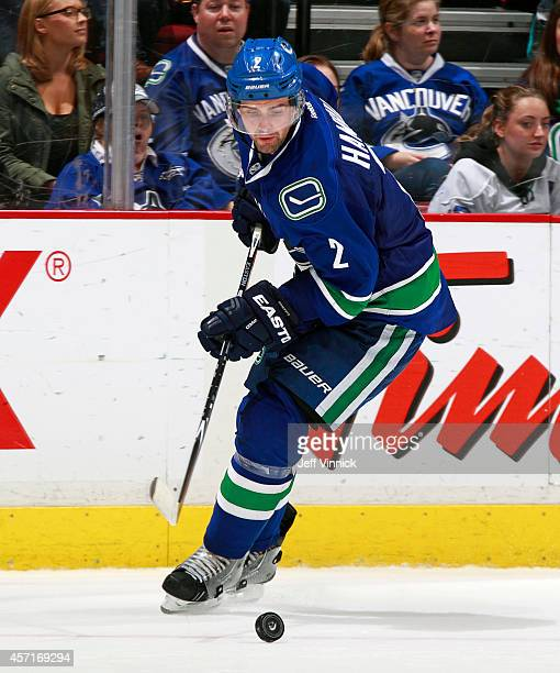 Dan Hamhuis of the Vancouver Canucks skates up ice with the puck during their NHL game against the Edmonton Oilers at Rogers Arena October 11, 2014...