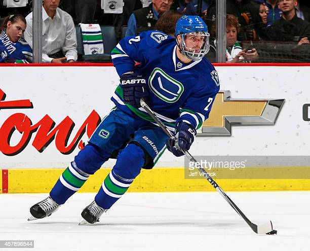 Dan Hamhuis of the Vancouver Canucks skates up ice with the puck during their NHL game against theTampa Bay Lightning at Rogers Arena October 18,...