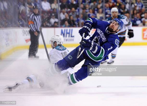 Dan Hamhuis of the Vancouver Canucks vies for the puck with Devin Setoguchi of the San Jose Sharks in the first period in Game One of the Western...