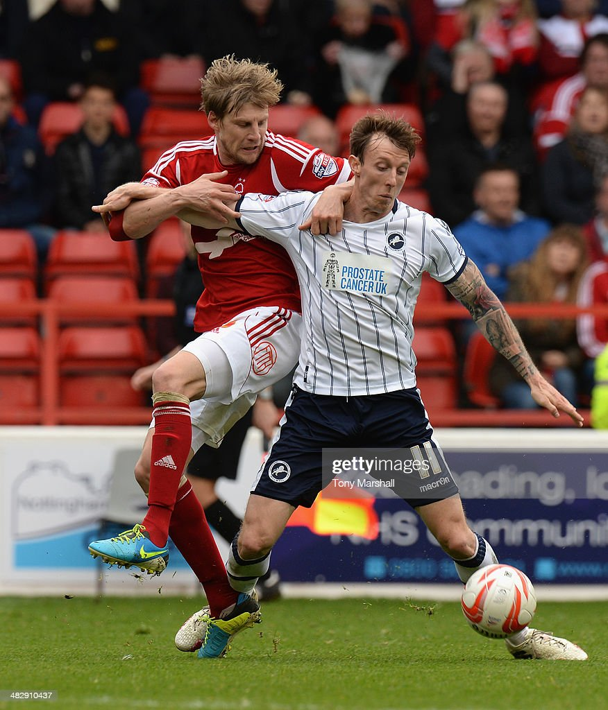 Dan Harding of Nottingham Forest challenges Martyn Woolford of Millwall during the Sky Bet Championship match between Nottingham Forest and Millwall at City Ground on April 05, 2014 in Nottingham, England,