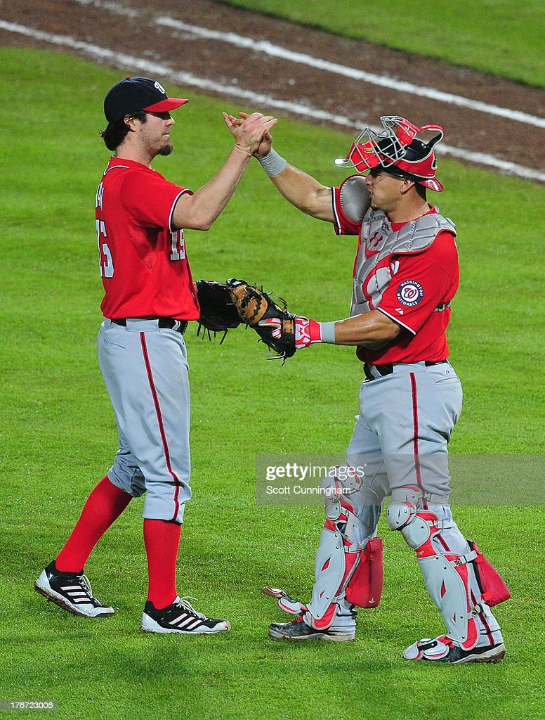 Dan Haren #15 and Wilson Ramos #40 (L-R) of the Washington Nationals celebrate after the game against the Atlanta Braves at Turner Field on August 17, 2013 in Atlanta, Georgia.
