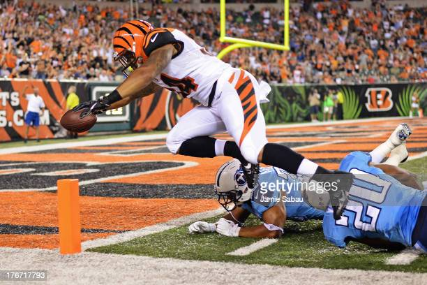 Dan Herron of the Cincinnati Bengals leaps in to the end zone to complete a 40yard touchdown run past Al Afalava of the Tennessee Titans and...