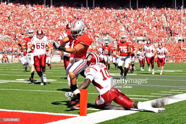 Dan Herron of the Ohio State Buckeyes steps over the tackle attempt of Donnell Jones of the Indiana Hoosiers to complete a 39-yard touchdown run in...
