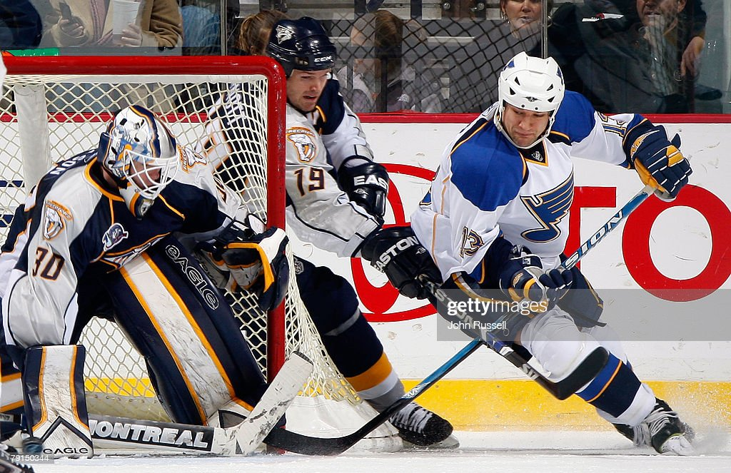 Dan Hinote #13 of the St. Louis Blues shoots the puck against Chris Mason #30 of the Nashville Predators and Jason Arnott #19 defends on January 21, 2008 at the Sommet Center in Nashville, Tennessee.