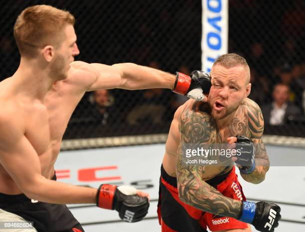 Dan Hooker of New Zealand punches Ross Pearson of England in their lightweight fight during the UFC Fight Night event at the Spark Arena on June 11...