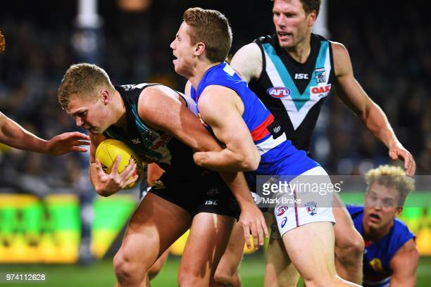 Dan Houston of Port Adelaide tackled by Lachie Hunter of the Bulldogs during the round 13 AFL match between Port Adelaide Power and the Western...