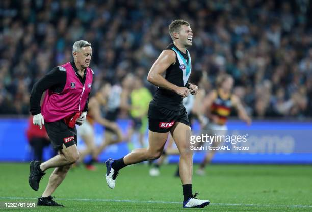 Dan Houston of the Power comes off with a shoulder injury during the 2021 AFL Round 08 match between the Port Adelaide Power and the Adelaide Crows...
