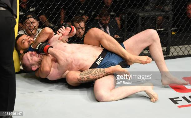 Dan Ige secures a rear choke submission against Danny Henry of Scotland in their featherweight bout during the UFC Fight Night event at The O2 Arena...