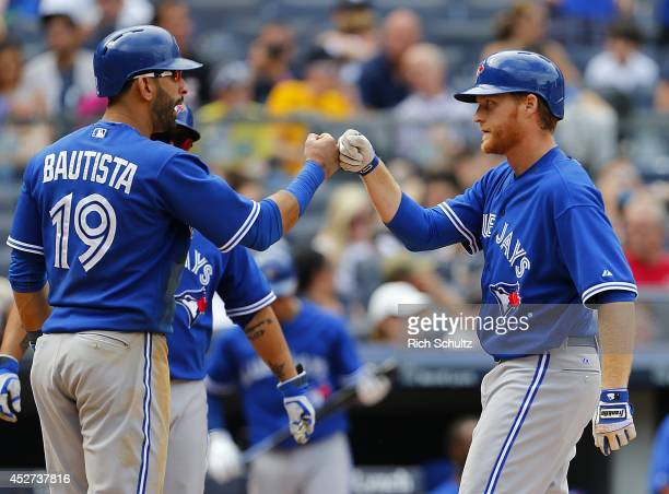 Dan Johnson of the Toronto Blue Jays is congratulated by teammate Jose Bautista after Johnson hit a threerun home run in the ninth inning against the...