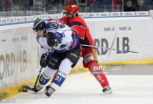Dan Lambert of Hannover and Rene Roethke of Ingolstadt compete for the puck during the DEL Bundesliga game between Hanover Scorpions and ERC...