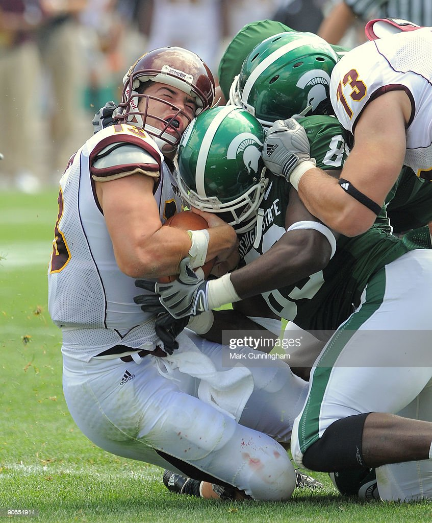 Dan LeFevour #13 of the Central Michigan Chippewas is sacked by the Michigan State Spartans defense during the game at Spartan Stadium on September 12, 2009 in East Lansing, Michigan. The Chippewas defeated the Spartans 29-27.