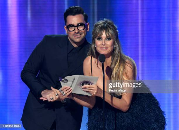 Dan Levy and Heidi Klum speak onstage during the 2019 American Music Awards at Microsoft Theater on November 24 2019 in Los Angeles California