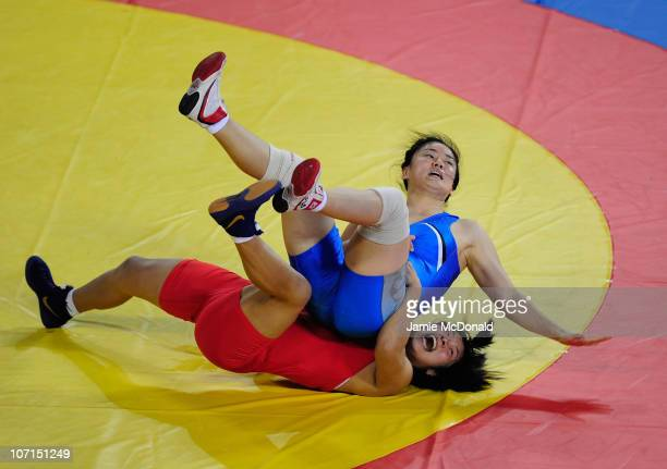 Dan Li of China throws Mikyoung Bae of Korea during the Women's Freestyle 72kg event at Huagong Gymnasium during day fourteen of the 16th Asian Games...