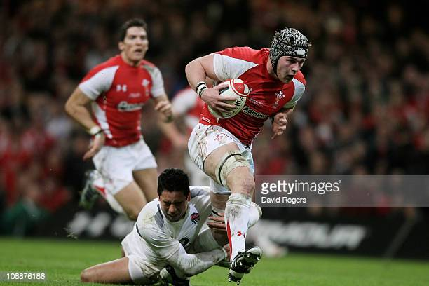 Dan Lydiate of Wales is tackled by Shontayne Hape of England during the RBS 6 Nations Championship match between Wales and England at the Millennium...