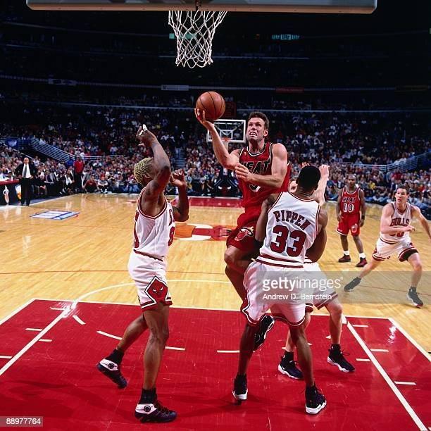 Dan Majerle of the Miami Heat goes up for a shot against Dennis Rodman and Scottie Pippen of the Chicago Bulls in Game One of the Eastern Conference...