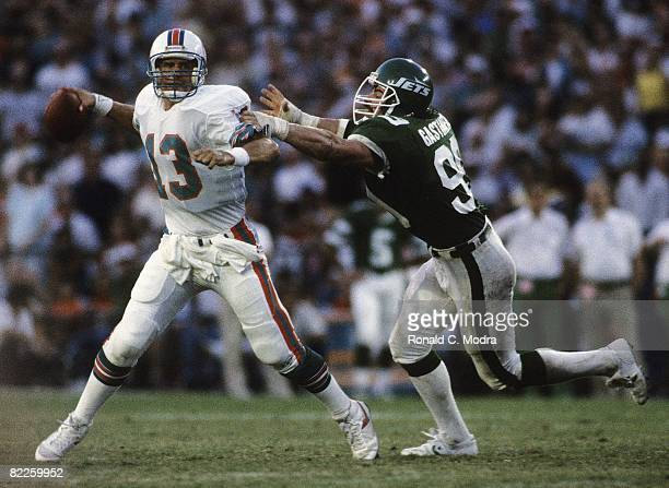 Dan Marino of the Miami Dolphins passes as Mark Gastineau of the New York Jets puts the pressure on during a NFL game on November 10 1985 in Miami...