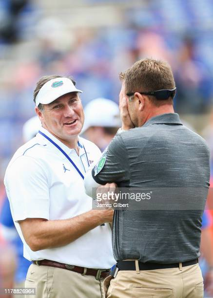 Dan Mullen head coach of the Florida Gators and Rob Ambrose head coach of the Towson Tigers meet before the start of a game at Ben Hill Griffin...