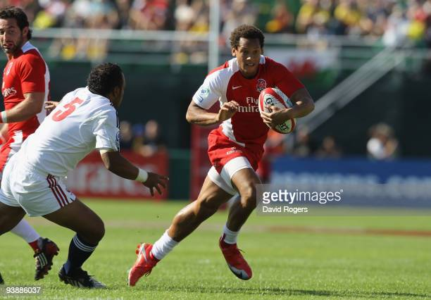 Dan Norton of England breaks away to score one of his three tries against the USA during the IRB Sevens tournament at the Dubai Sevens Stadium on...