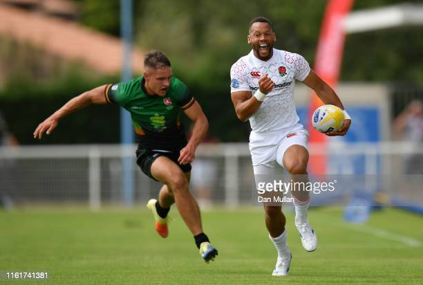 Dan Norton of England makes a break past Matas Miezys of Lithuania to score a try during the Group C match between England and Lithuania on day one...