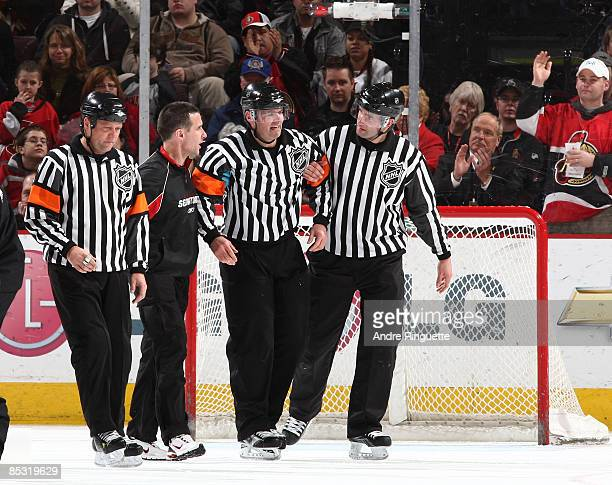 Dan O'Halloran Gerry Townend and Steve Miller help Stephane Auger off the ice for medical attention in an NHL game between the Ottawa Senators and...