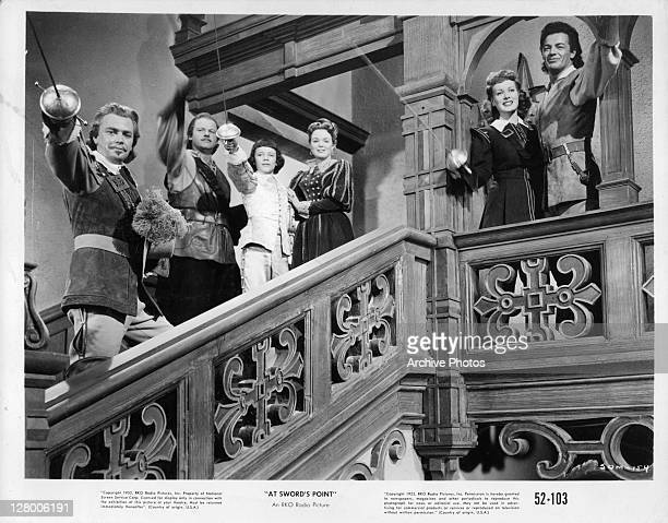 Dan O'Herlihy , Alan Hale Jr , Maureen O'Hara , and Cornel Wilde , with others, raise swords in a scene from the film 'At Sword's Point', aka 'Sons...