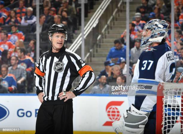 Dan O'Rourke discusses the play with Connor Hellebuyck of the Winnipeg Jetsskates during the game against the Edmonton Oilers on October 9 2017 at...