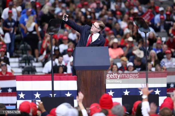 Dan Patrick Texas' lieutenant governor uses a mobile device to take a 'selfie' photograph while on stage during a rally with US President Donald...