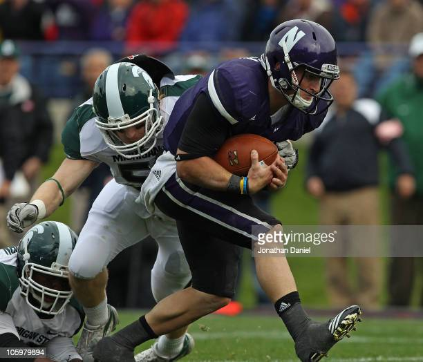 Dan Persa of the Northwestern Wildcats runs past Eric Gordon of the Michigan State Spartans for a touchdown at Ryan Field on October 23, 2010 in...