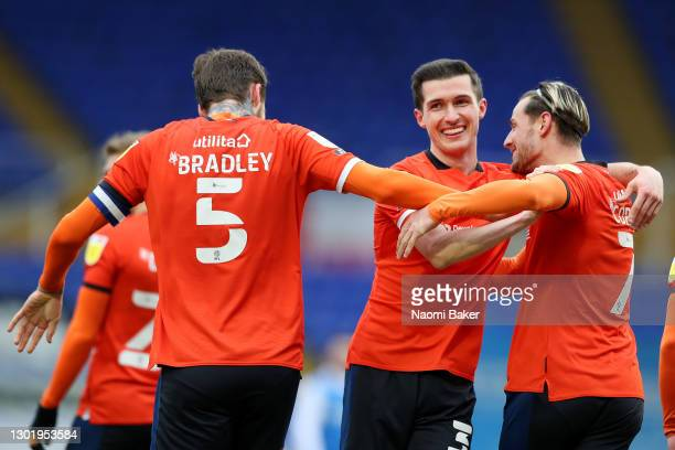 Dan Potts of Luton Town celebrates with teammates Sonny Bradley and Harry Cornick after scoring his team's first goal during the Sky Bet Championship...