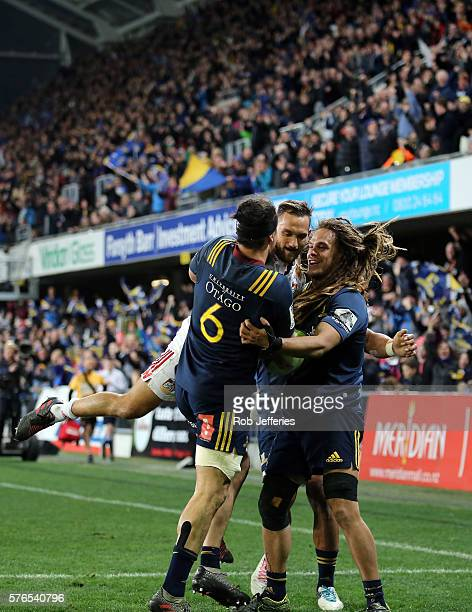 Dan Pryor of the Highlanders celebrates his try with his teammates and Aaron Cruden of the Chiefs during the round 17 Super Rugby match between the...
