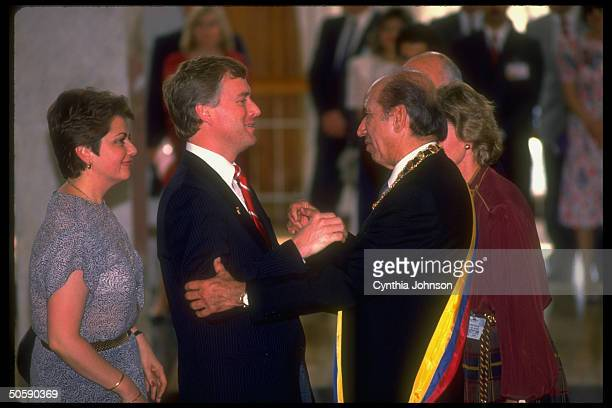 VP Dan Quayle embracing inauguralsashed Pres Carlos Andres Perez flanked by others attending takingofoffice ceremony