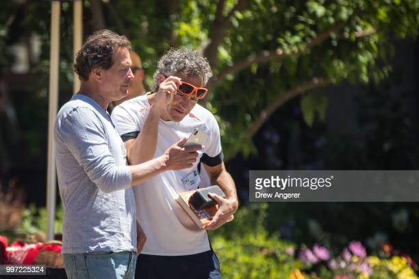 Dan Schulman president and chief executive officer of PayPal Inc and Alex Karp chief executive officer of Palantir Technologies talk with each other...