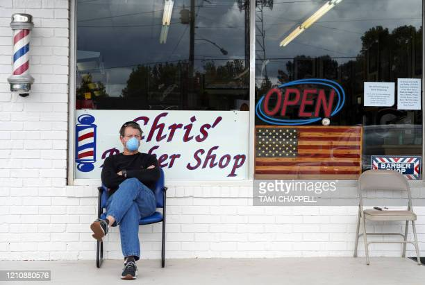Dan Settle sits outside Chris' Barber Shop as he waits his turn for a haircut in Lilburn, Georgia on April 24, 2020. - Georgia Governor Brian Kemp...