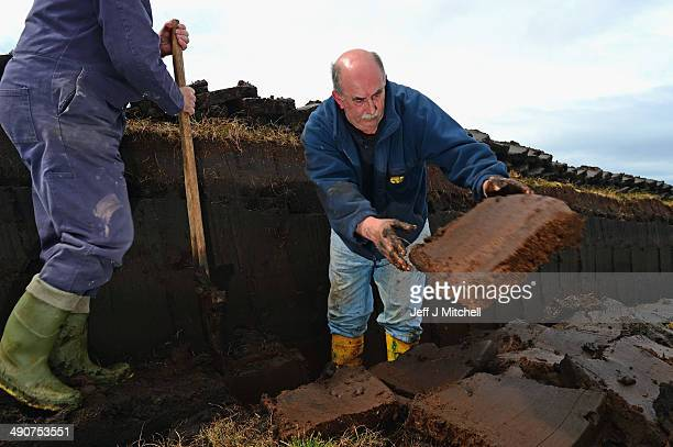 Dan Smith and Donald Campbell, extract peat from a moor near the village of Cross on May 14, 2014 in Lewis, Scotland. The tradition of peat cutting...