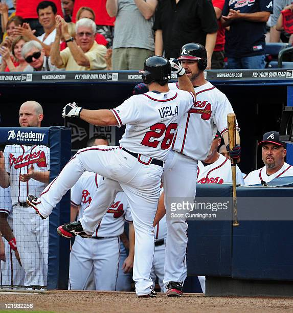 Dan Uggla of the Atlanta Braves is congratulated by David Ross after hitting a home run against the Arizona Diamondbacks at Turner Field on August 20...